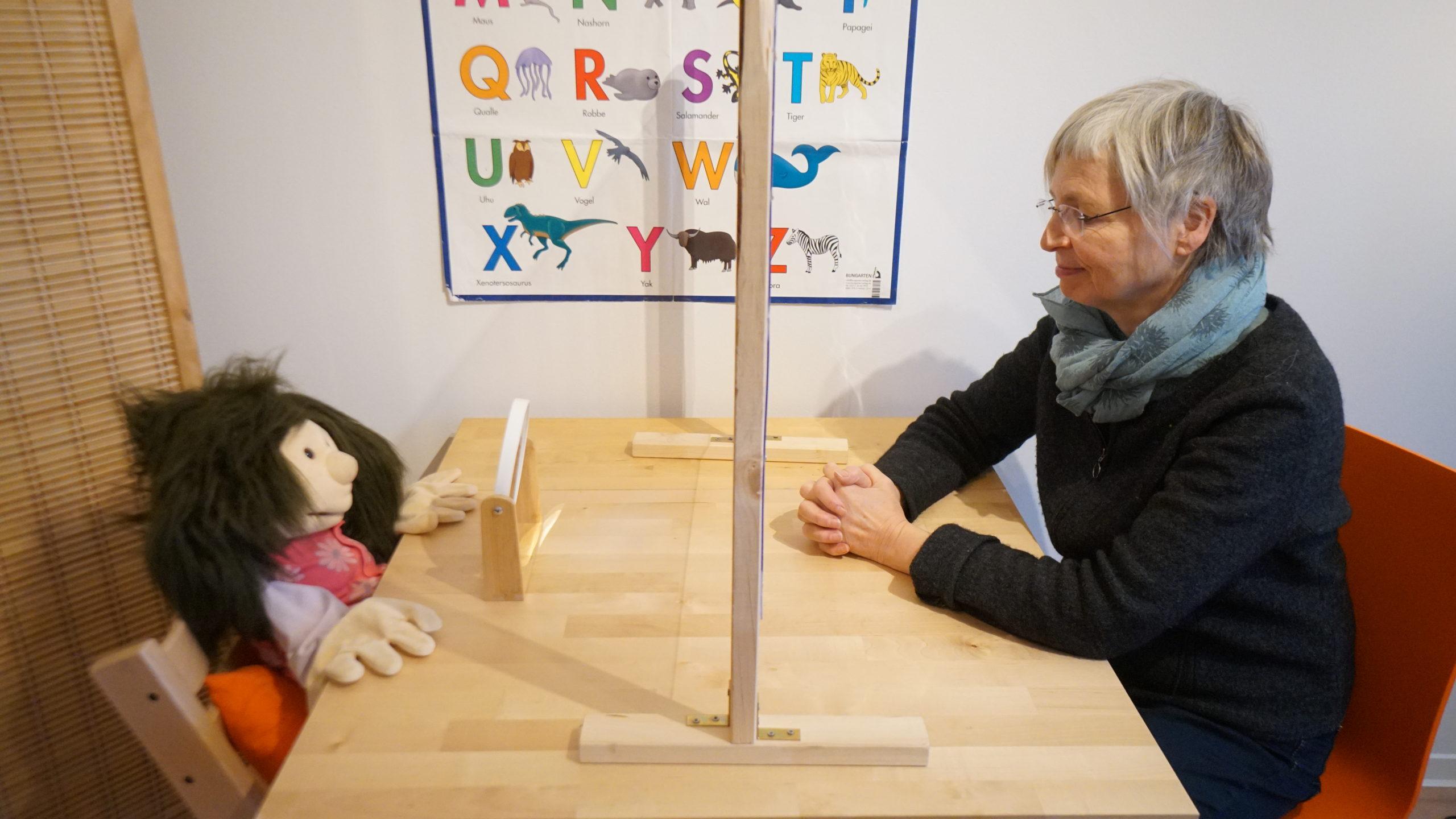 Sabine Goffart und eine große Handpuppe sitzen am Behandlungstisch